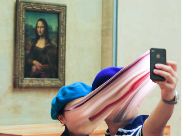 Two tourists standing in front of the Mona Lisa are distorted by the digital effect.