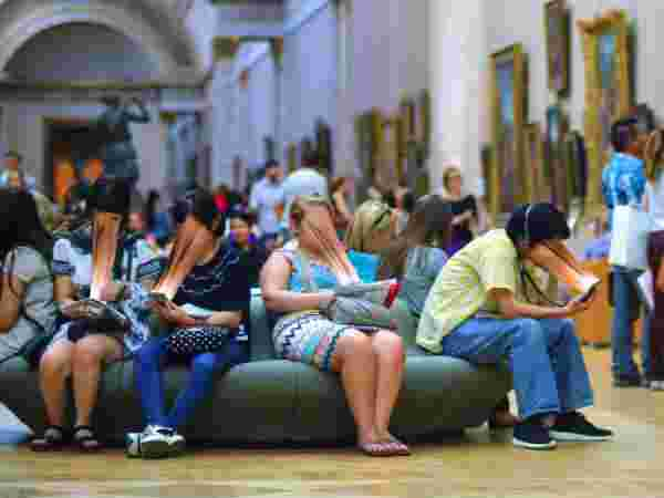 A group of tourists prefer their smartphones to the art surrounding them in the museum.