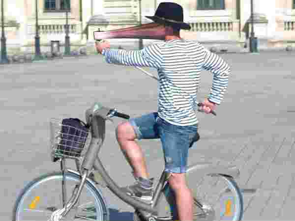 While a cyclist takes a photo using a selfie stick, his face is warped by the stretched effect.